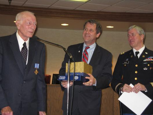 Senator Brown presents Major D. Brock Foster, USAF Retired, with the Distiguished Flying Cross